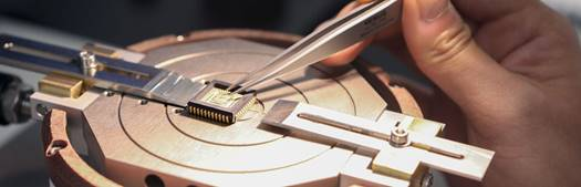 Zoomed in view of a microchip being adjusted with tweezers